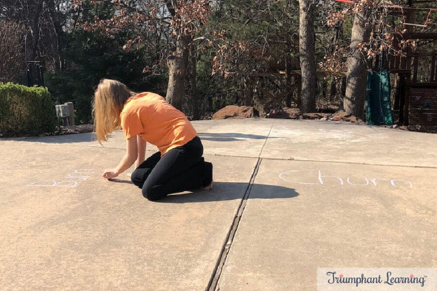 Practicing spelling words with sidewalk chalk. She underlined patterns in the words to help her remember the spelling.
